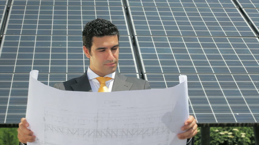 Businessman reading blueprints in solar power station (series)