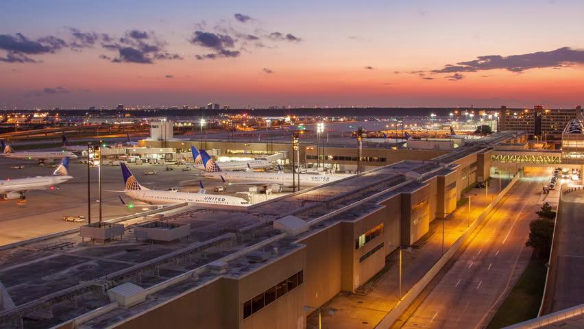 HOUSTON, TX - 2014: George Bush Intercontinental Airport IAH Timelapse with a Medium Pan towards Terminal C at Dusk Sunset in Houston Texas