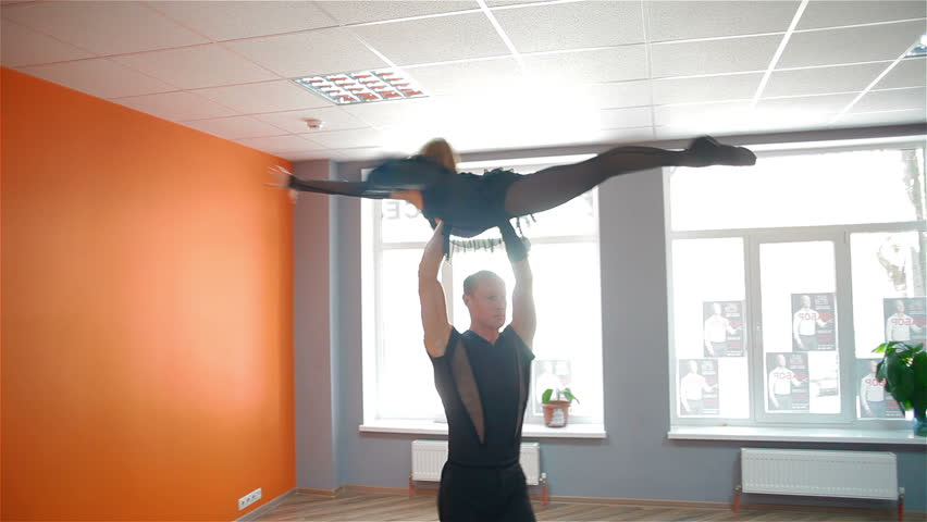 A pair of professional dancers trained in dance studio. They work out the complicated dance techniques and movements