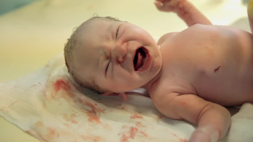 Just-born baby is crying on a table. Just-born baby is crying on a table and need a hug and worm blanket