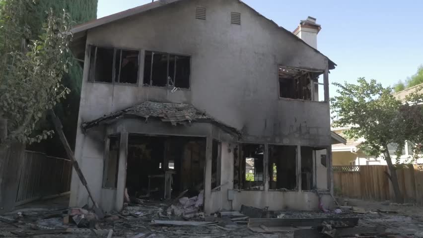 Cinematic dolly shot of exterior aftermath of a two alarm fire in a residential home. | Shutterstock HD Video #7751362