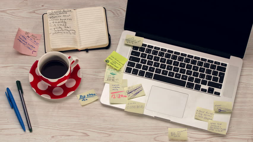 Home office desk with notebook, laptop and coffee covered with post it papers - stop motion animation and 4K timelapse.