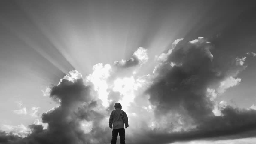 Silhouetted person stands in front of beautiful cloudscape with heavenly sun break, black and white.