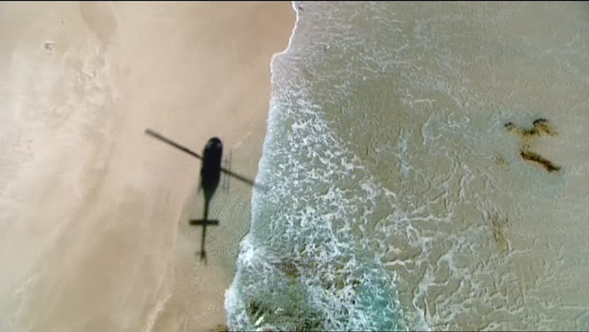 Shadow or Silhouette of Helicopter flying along Beach. Great for abstracts, war, transport, beach patrol or scene changer