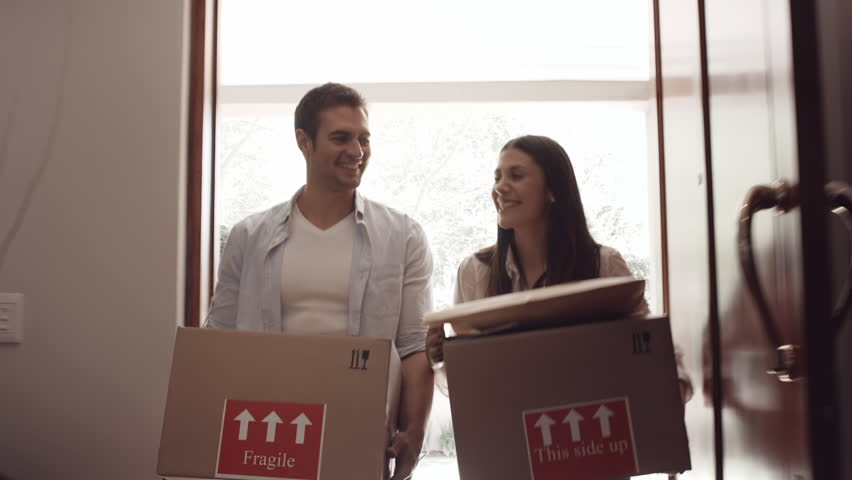 Young couple picking up moving boxes and walking through their door of new apartment while moving in.  #7783174