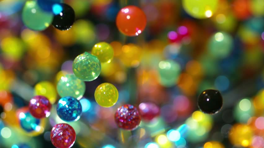 Bouncy Ball Rainbow - High speed macro shot of colorful bouncy balls falling against a reflective surface.