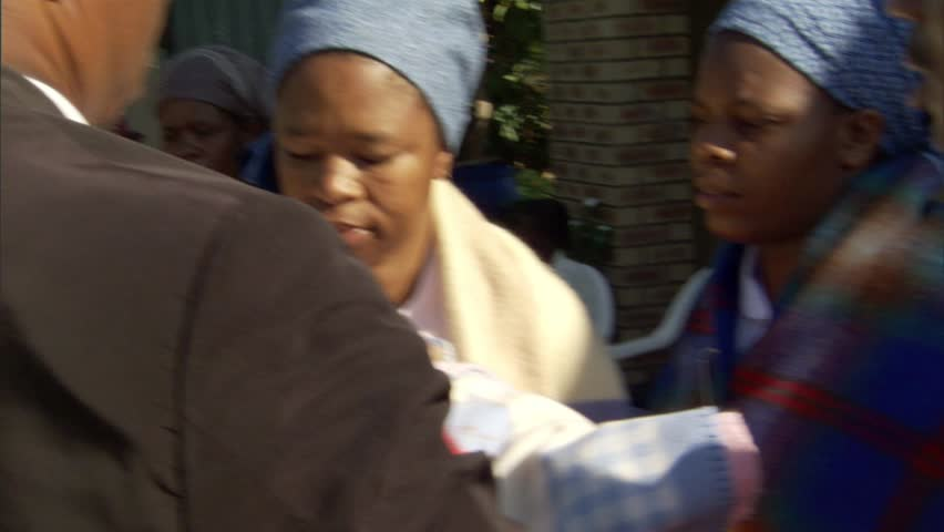 Woman holding a baby while others sing at a baby naming party in Gaborone, Botswana, | Shutterstock HD Video #7810972