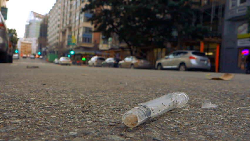 Broken syringe lying on an inner city street with traffic and blurred buildings beyond.