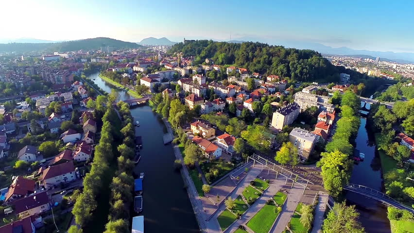 Aerial shot of Ljubljana city with Ljubljanica and castle at sunset. Flying above beautiful city with landscape view of river, castle and green hills. Royalty-Free Stock Footage #7851247