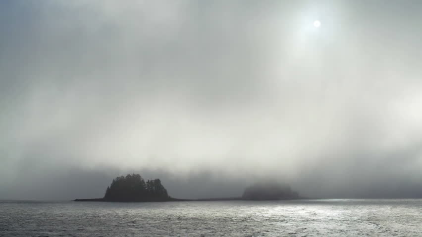 Twin gumdrop islands in Southeast Alaska barely visible as the weak sunlight filters through heavy fog on teh water. #7853131