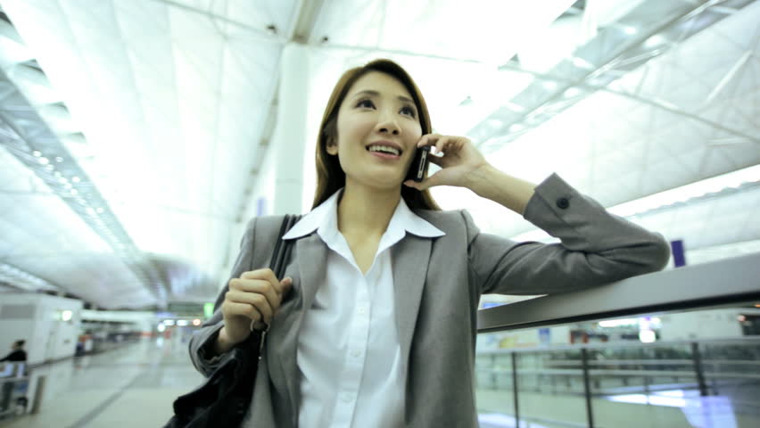 Asian Chinese businesswoman global traveller airport arrival departures hall business smart phone text wireless technology communications | Shutterstock HD Video #7853932