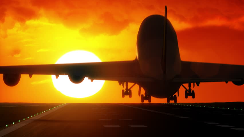 Jet plane lands on airport runway as silhouette in front of large sunset / sunrise 4K UltraHD #7859374