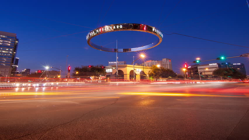 HOUSTON TX - 2014: Galleria Timelapse of Traffic during Sunset at Westheimer and Post Oak Boulevard Intersection with Fast Moving Lights on a Vibrant Colored Texas Evening