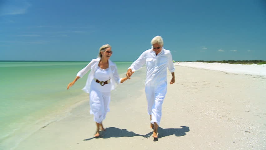 Attractive senior carefree couple running along the beach barefoot enjoying a fun lifestyle 60FPS