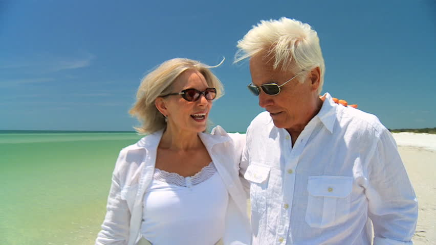 Attractive senior couple enjoying each others company walking on the beach 60FPS