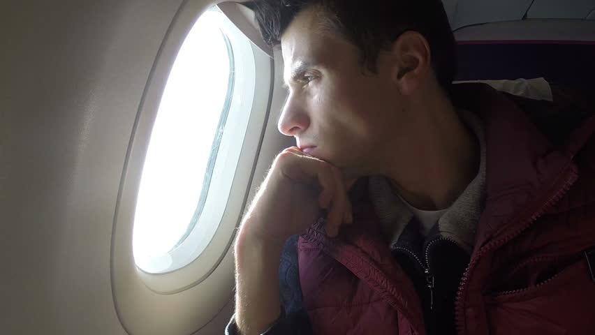 Bored airplane passenger porthole look long flight nothing to do
