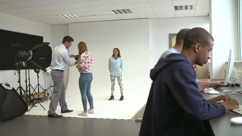 Teacher helping photography students to take pictures of one another in studio. Shot on Sony FS700 at frame rate of 25fps #7904938