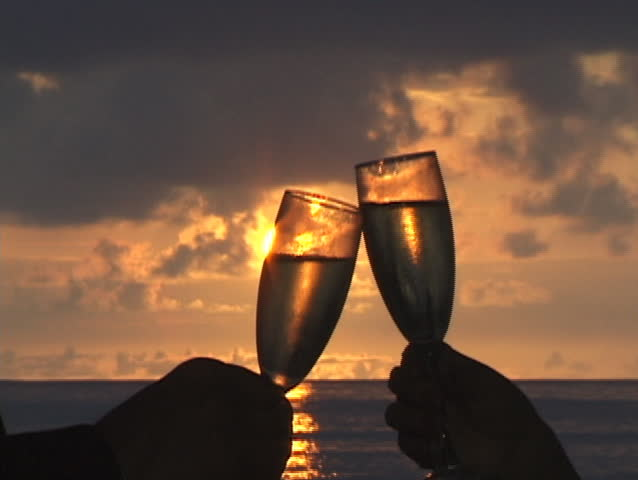 Champagne toast with sunset background.
