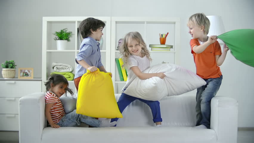 Four kids playing on sofa pillow fighting  | Shutterstock HD Video #7920406
