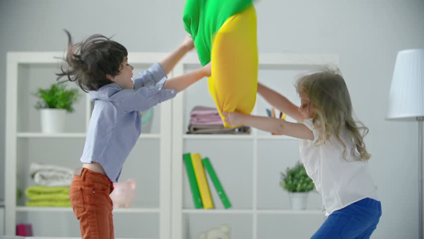 Two adorable kids misbehaving pillow fighting | Shutterstock HD Video #7920421
