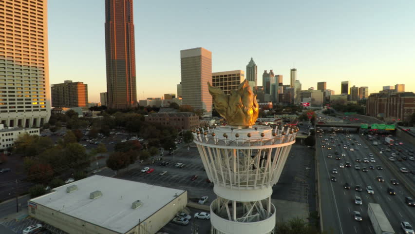 Atlanta cityscape aerial flying around large torch monument statue.