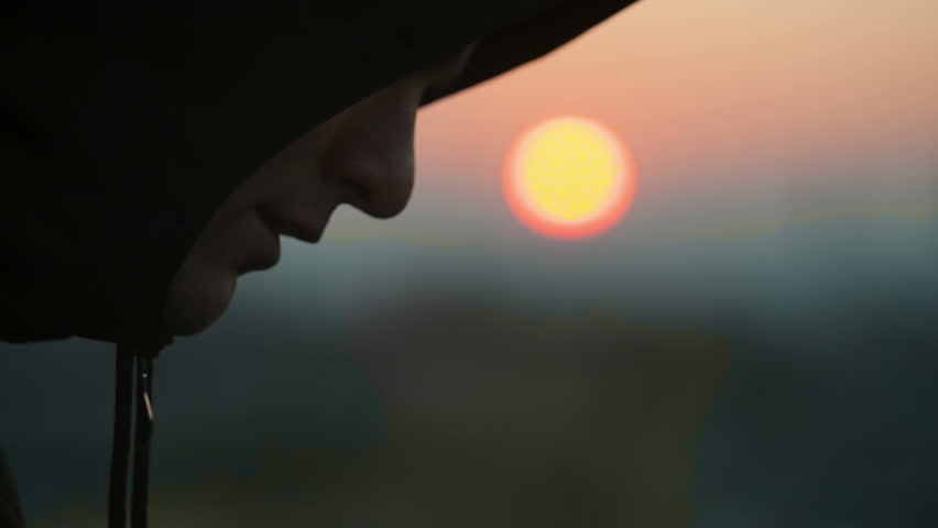 Sad young man in the hood at sunset. RAW video record.