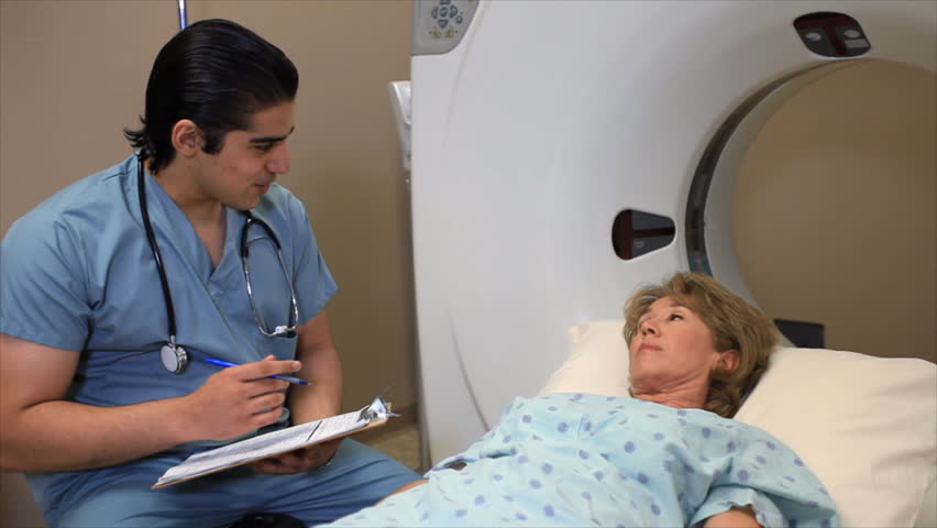A technician asking a patient questions and filling out paperwork before a cat scan.