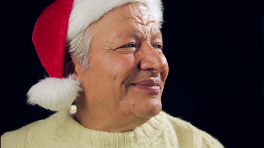 Close up of a smiling male pensioner with red Santa Claus cap and warm pullover. He is raising a small wrapped present and later pointing at it. Reminder for gift giving occasions. Black background. | Shutterstock HD Video #7962199