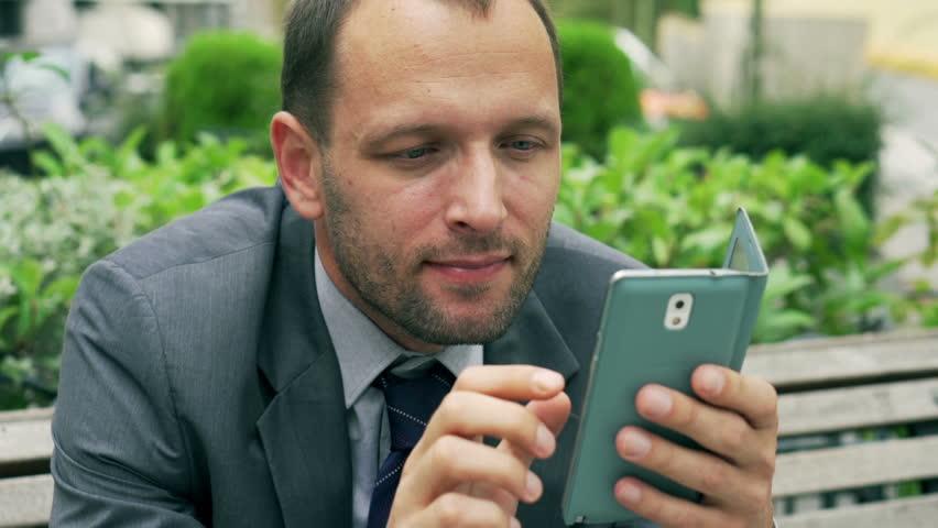 Businessman holding cellphone and smiling, closeup, steadycam shot  | Shutterstock HD Video #7968361