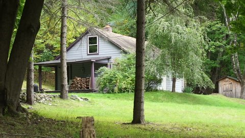 A cottage in the woods, nestled in some trees. Tracking reveal. Property released establishing shot