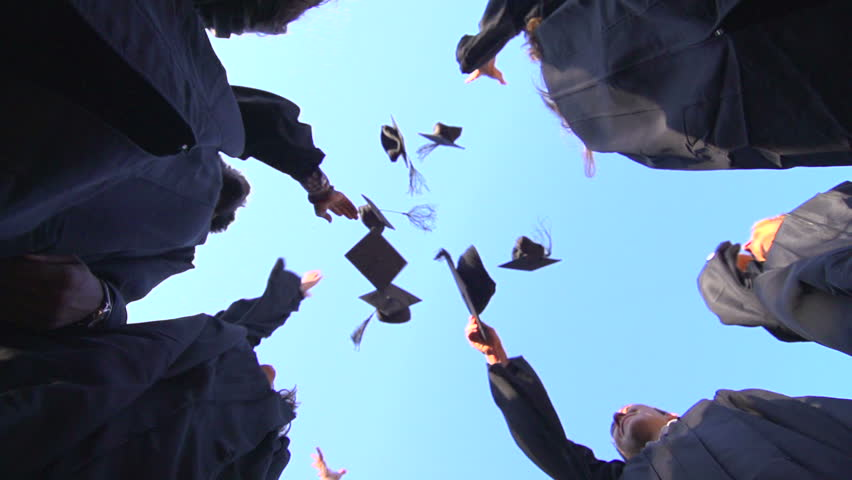 A slow-motion shot from below of a group of racially-diverse students throwing their graduation mortarboards in the air in celebration.