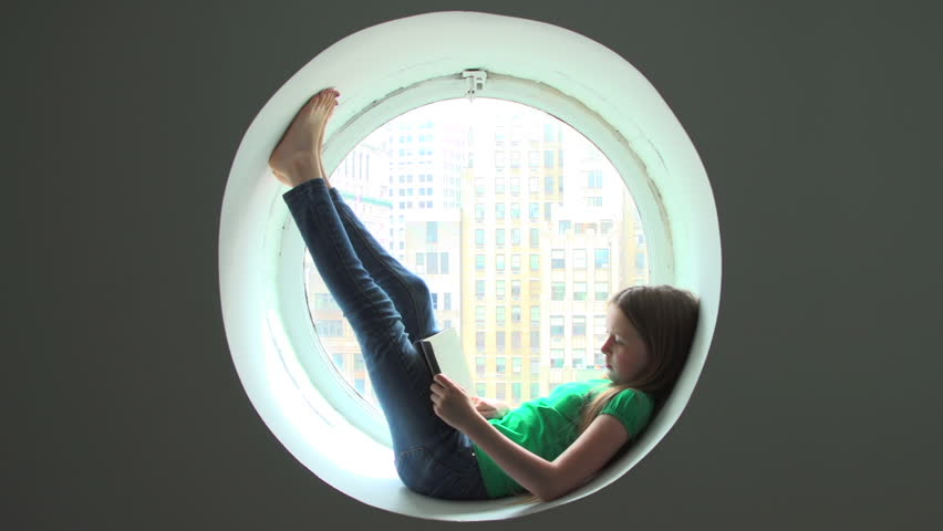 Girl lies in a round window reading a book. Behind her is a city skyline. | Shutterstock HD Video #7973062