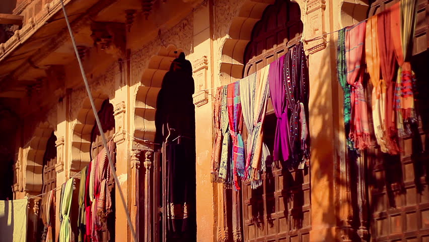 An Haveli entrance on Jaisalmer Fort, with elaborately sculpted sandstone columns, and colorful pashminas shawls swaying with the wind. Golden sunset light on a locked down camera shot.