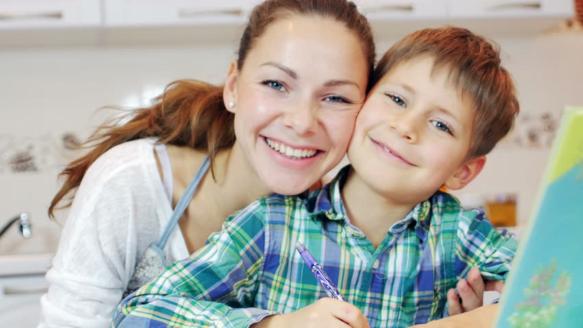 Little boy doing homework in the kitchen while his mother is engaged in household chores. He writes, his mom came up to him, they laugh, then looking at the camera together. They look very happy