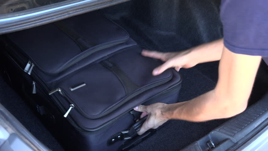 Man packs luggage into car trunk for family car trip. 4K UHD 3840x2160