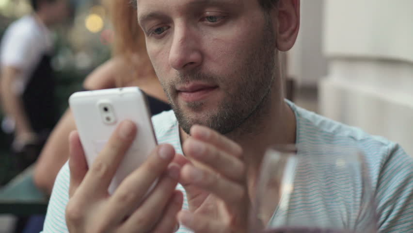 Young man using smartphone and drinking red wine in cafe  | Shutterstock HD Video #8016316