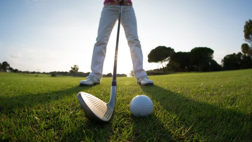 Golfer hitting golf ball, waist down shot