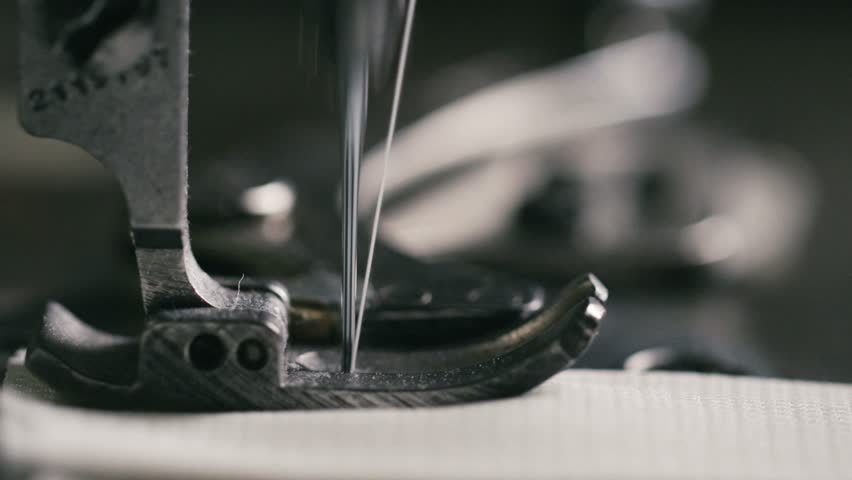 Super slow motion of vintage sewing machine stitching on white fabric (macro close up)