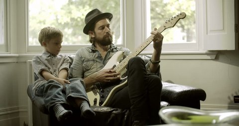 Father teaching guitar to his son in domestic room