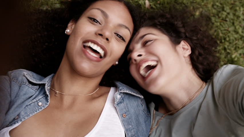 Best girl friends lying on grass and having fun taking a selfie with smart phone