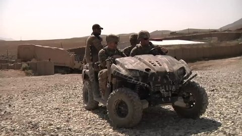 KAPISA PROVINCE AFGHANISTAN, AUGUST 2013, ISAF soldiers drive with a ATV quad through a door in a Afghan camp.