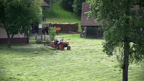 Person on tractor turning grass in slow motion. Drying grass with tractor and mixer in slow motion.