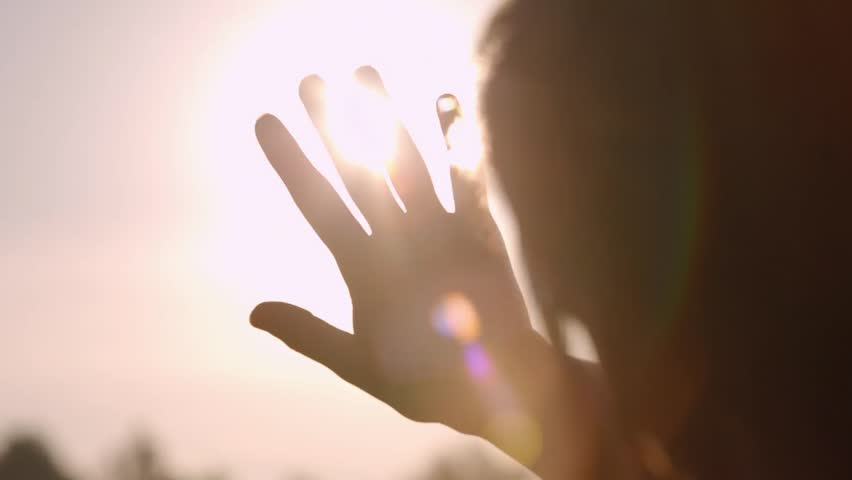 Girl looks at the sun through her hand #8079799