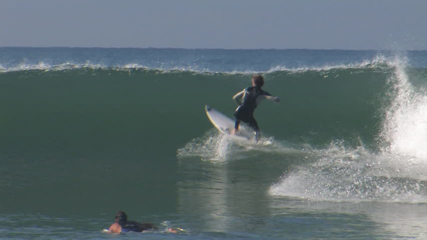 A surfer performs tricks and turns on a nice little wave   Shutterstock HD Video #8099248