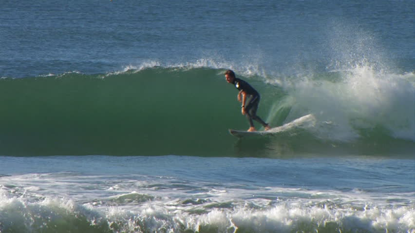 A surfer rides on a small wave   Shutterstock HD Video #8099401
