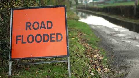 Road flooded sign and man with dog not being able to proceed