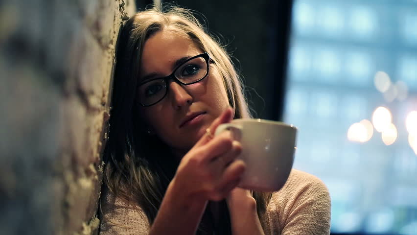Young, pretty, sad woman drinking tea in cafe
