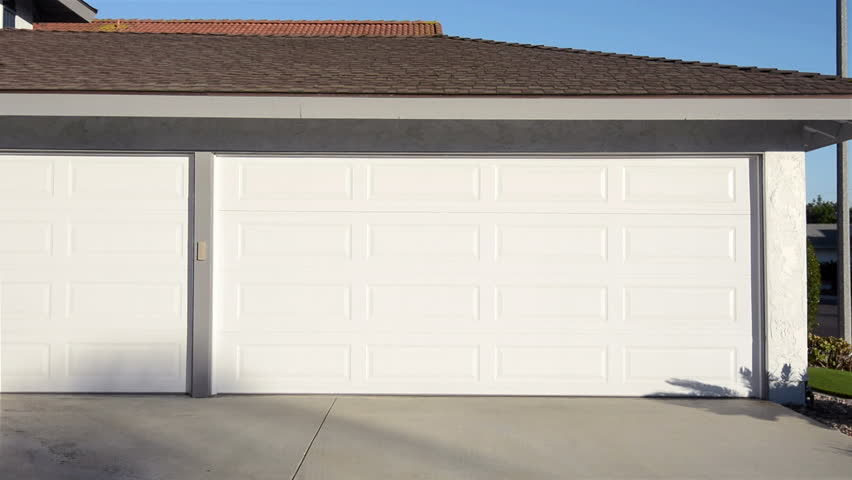 A residential home with an automatic roll up garage door moving in the opening position. | Shutterstock HD Video #8157040