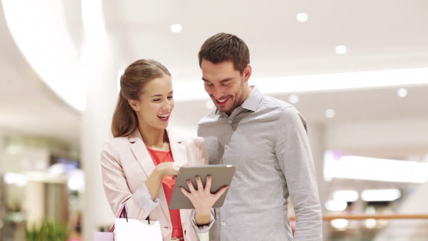 Sale, consumerism, technology and people concept - happy young couple with shopping bags and tablet pc computer talking in mall | Shutterstock HD Video #8169931