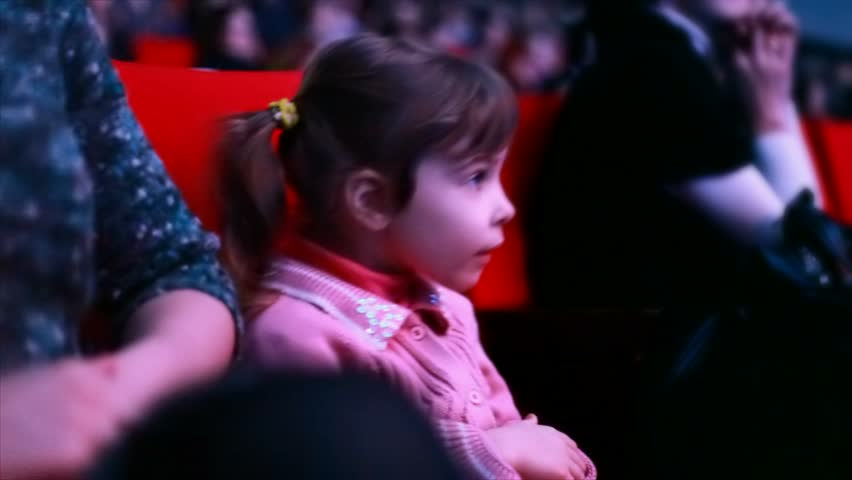 Impressionable little girl sits on a red chair in auditorium of circus, watches a show and claps